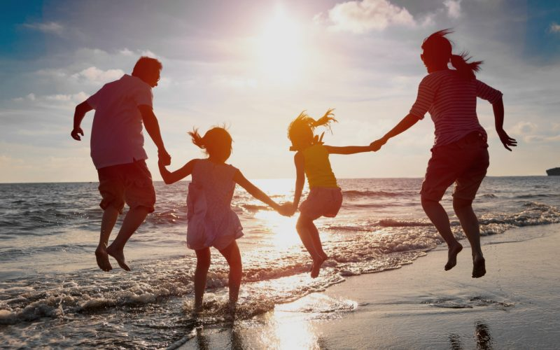 happy-family-jumping-together-on-beach